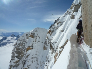 Niall McCann on a stance in deep powder on the Cosmiques Arête.