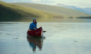 Finn McCann canoeing on Glacier Lake with the arriving float plane just visible behind him
